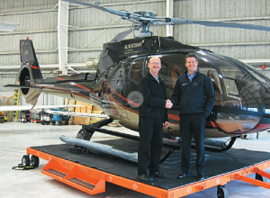Vector's Regional Sales Director for Western Canada, Eric Hicks (left), and Blackcomb's President and COO, Jonathan Burke, shake hands in front of a Eurocopter EC13084.  Photo courtesy of Vector Aerospace.